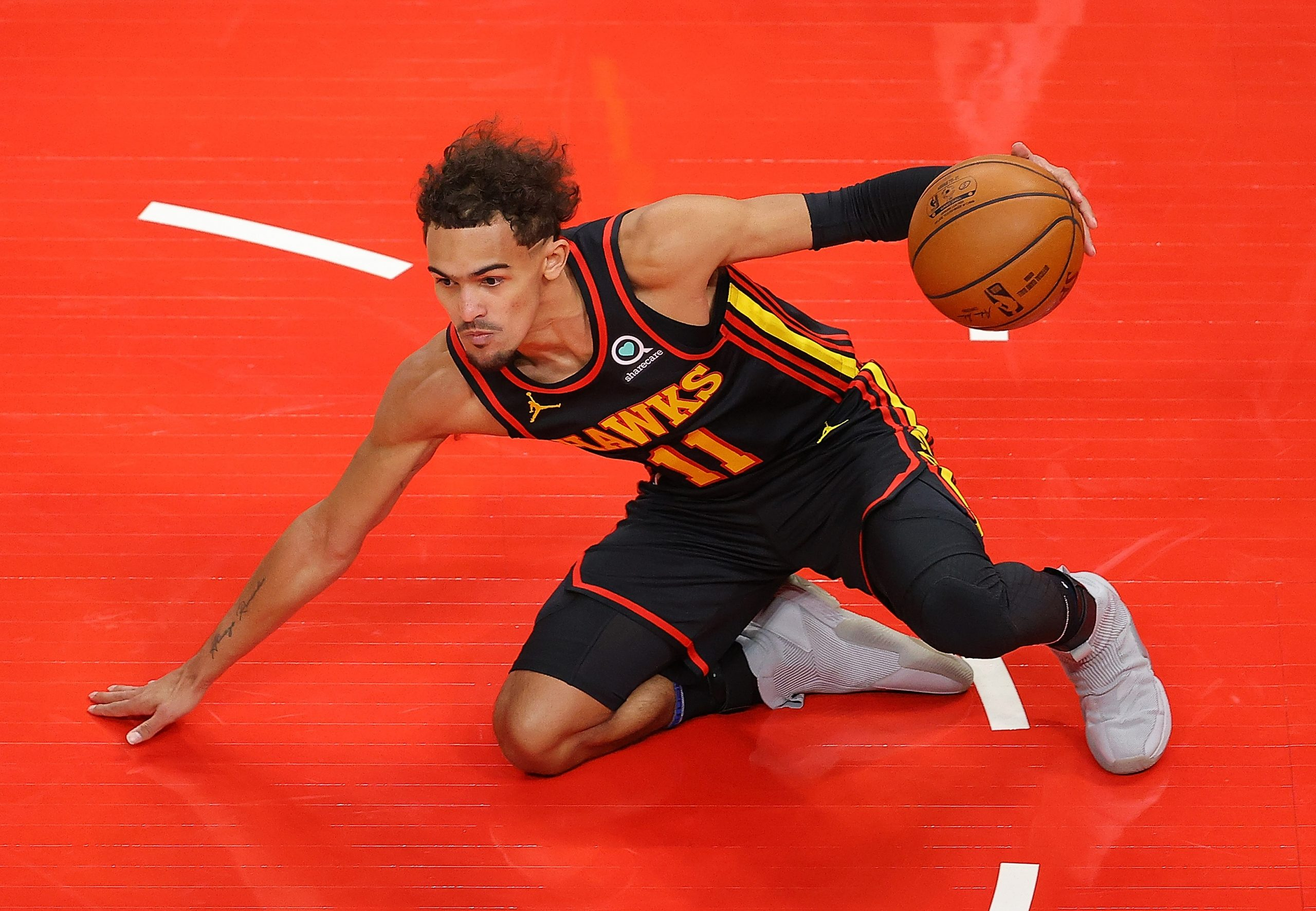 ATLANTA, GEORGIA - FEBRUARY 01:   Trae Young #11 of the Atlanta Hawks slips to the floor as he dribbles against the Los Angeles Lakers during the first half at State Farm Arena on February 01, 2021 in Atlanta, Georgia.  NOTE TO USER: User expressly acknowledges and agrees that, by downloading and or using this photograph, User is consenting to the terms and conditions of the Getty Images License Agreement.  (Photo by Kevin C. Cox/Getty Images)