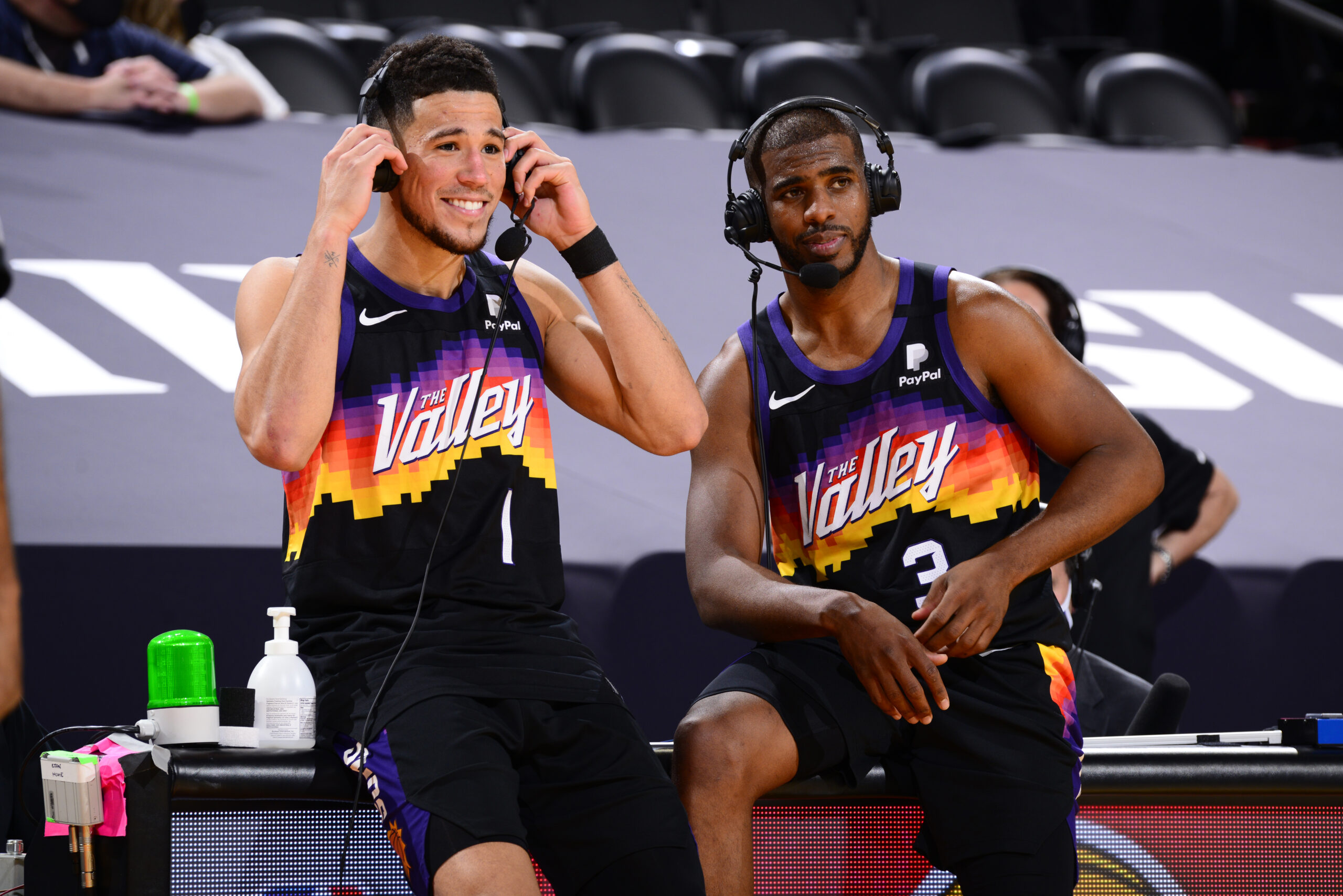 PHOENIX, AZ - APRIL 7: Devin Booker #1 and Chris Paul #3 of the Phoenix Suns get interviewed after the game against the Utah Jazz on April 7, 2021 at Phoenix Suns Arena in Phoenix, Arizona. NOTE TO USER: User expressly acknowledges and agrees that, by downloading and or using this photograph, user is consenting to the terms and conditions of the Getty Images License Agreement. Mandatory Copyright Notice: Copyright 2021 NBAE (Photo by Barry Gossage/NBAE via Getty Images)
